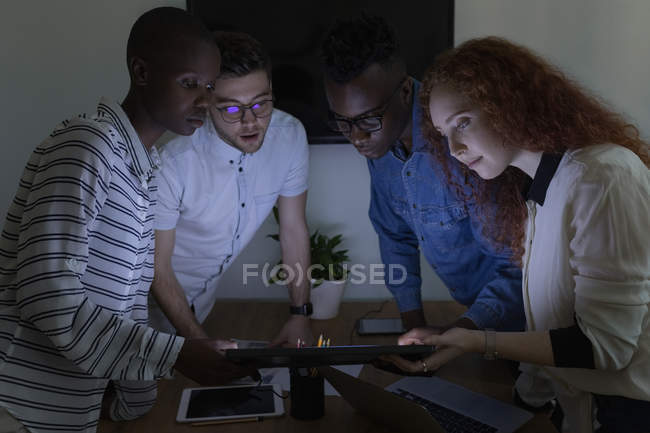 Executives discussing over digital tablet in conference room at office — Stock Photo