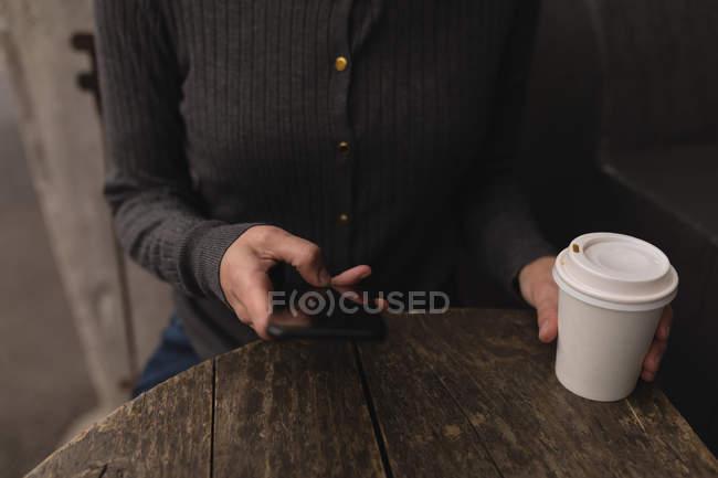 Середине раздел женщины, используя мобильный телефон в открытом кафе — стоковое фото