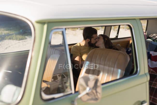 Романтическая пара целуется в фургоне во время дорожной поездки — стоковое фото
