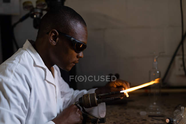 Side view of worker using welding torch in glass factory — Stock Photo
