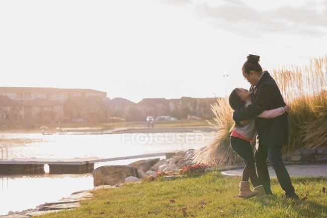 Grandmother and granddaughter hugging each other near lake side — Stock Photo
