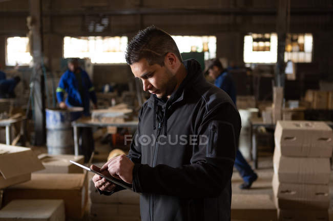 Attentive man using digital tablet in foundry — Stock Photo
