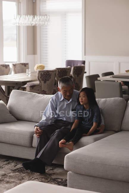 Дедушка и внучка общаются друг с другом на диване в гостиной дома — стоковое фото
