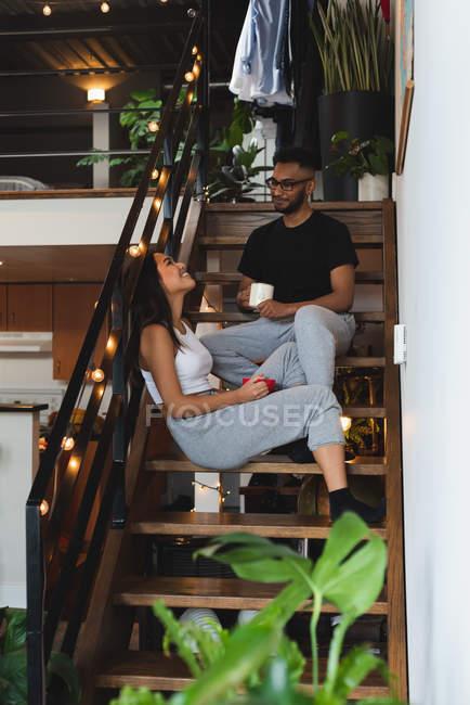 Пара взаимодействует друг с другом за чашечкой кофе на лестнице дома — стоковое фото