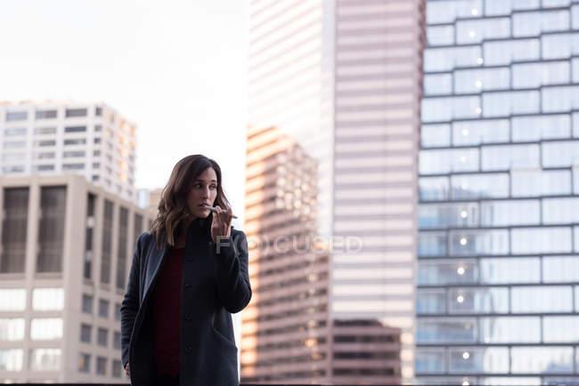 Empresária conversando no telefone celular na varanda do hotel — Fotografia de Stock