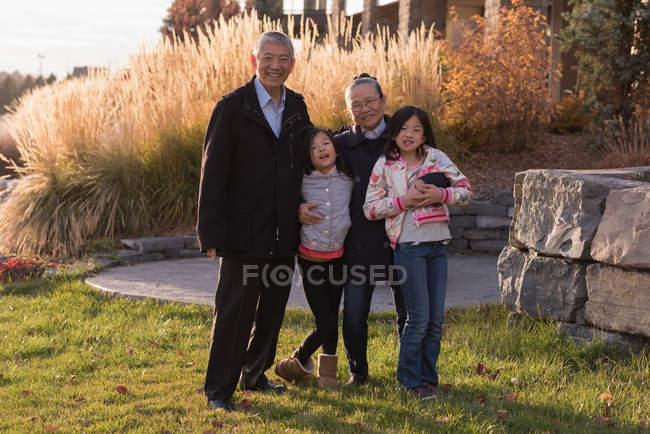 Großeltern und Enkelinnen Blick in die Kamera an einem sonnigen Tag — Stockfoto