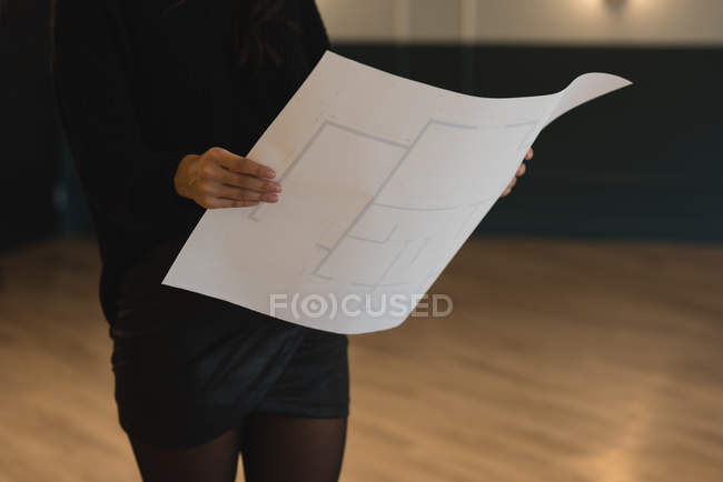 Mid section of businesswoman holding blueprint in office — Stock Photo