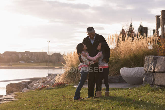 Grandfather and granddaughters hugging each other near lake side — Stock Photo