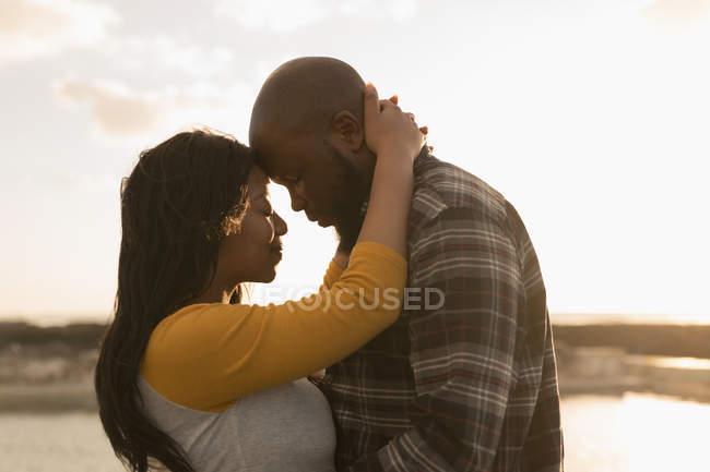 Romántica pareja abrazándose en la playa - foto de stock