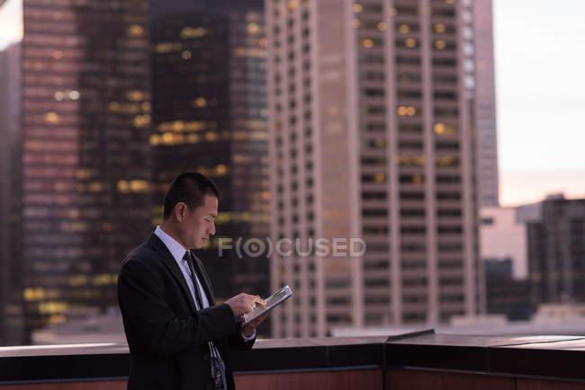 Uomo d'affari che utilizza tablet digitale in balcone in hotel — Foto stock