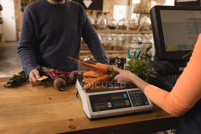 Mid section of customer making payment with credit card at counter — Stock Photo