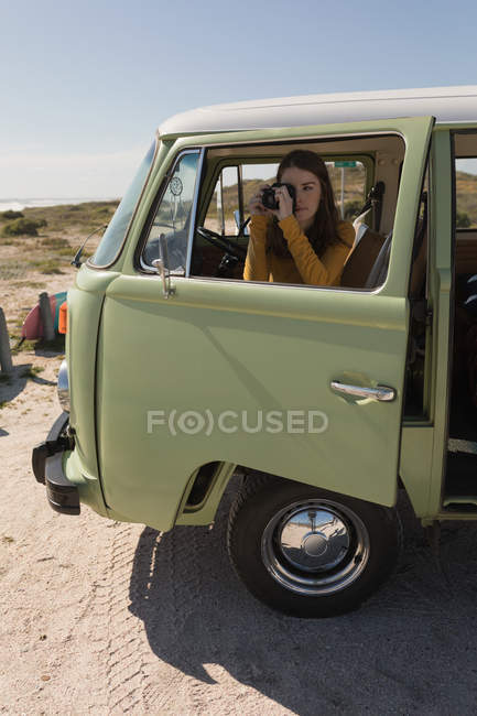 Woman taking photo from van on road trip — Stock Photo