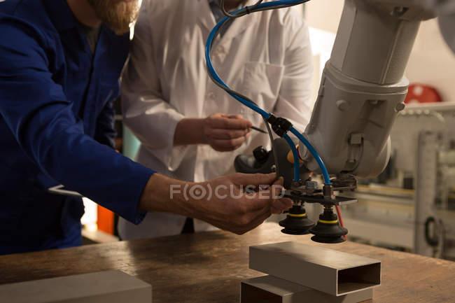 Робототехнические инженеры тестирования роботизированной машины на складе — стоковое фото