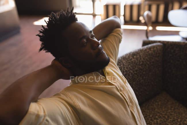 Homme exécutif relaxant avec les mains derrière la tête à la cafétéria au bureau — Photo de stock