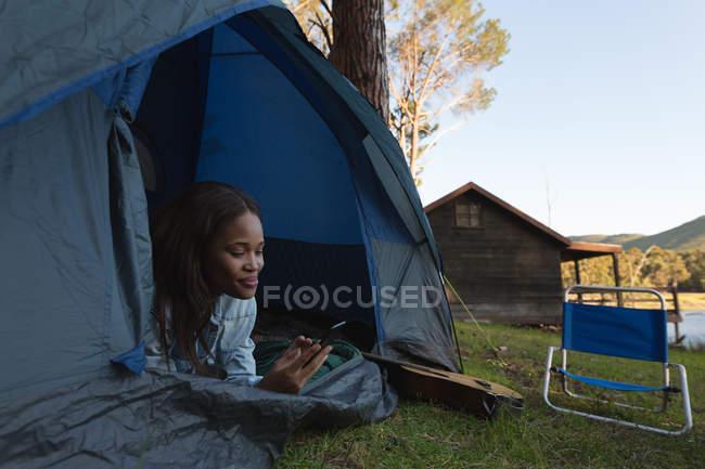 Frau benutzt Handy im Zelt auf Campingplatz — Stockfoto