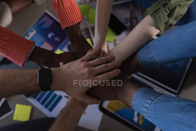 Cropped image of executives forming hands stack in office — Stock Photo