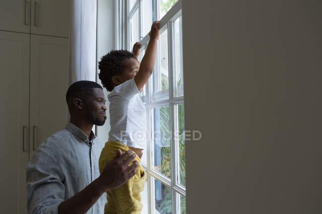 Батько і син, стоячи біля вікна будинку — стокове фото