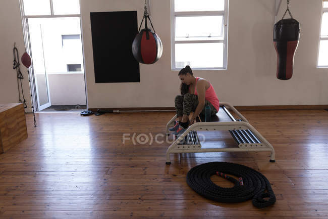 Female boxer tying shoe laces in fitness studio — Stock Photo