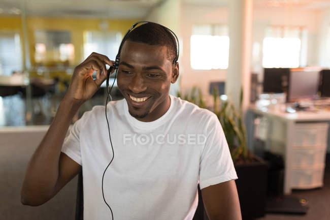 Улыбаясь, Бизнес Исполнительный говорить с клиентом в гарнитуру — стоковое фото