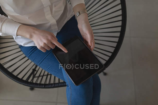 Midsection of female executive using digital tablet in office — Stock Photo