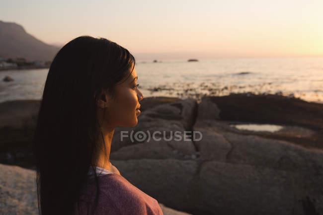 Vista lateral da mulher de pé perto do lado do mar — Fotografia de Stock