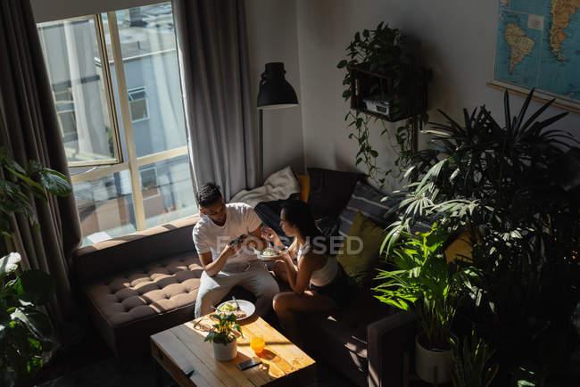 Мужчина фотографирует женщину, имеющую еду с мобильного телефона в гостиной дома — стоковое фото