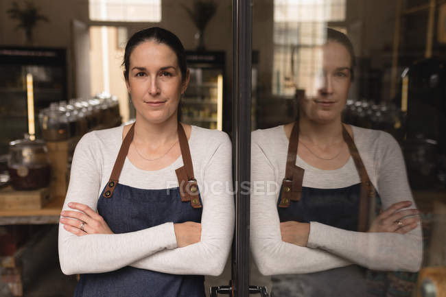 Portrait of female staff standing with arms crossed in supermarket — Stock Photo