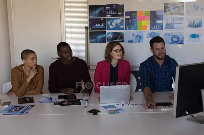 Dirigenti aziendali che guardano il PC desktop durante la riunione in ufficio — Foto stock