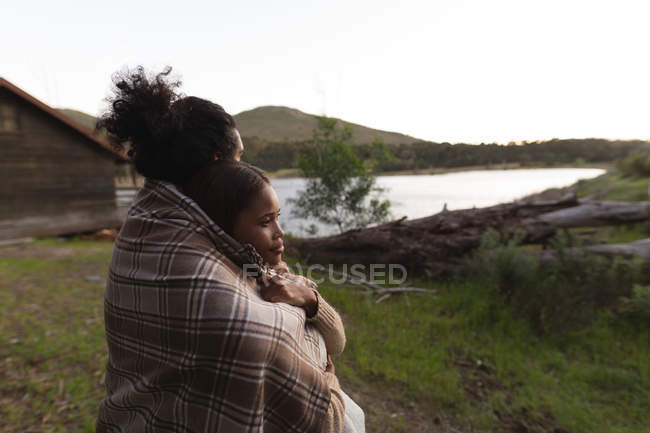 Romantic couple wrapped in blanket at campsite — Stock Photo