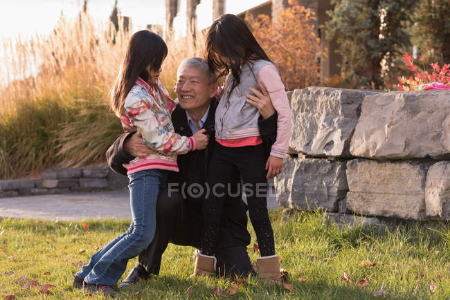 Happy grandfather embracing his granddaughters on a sunny day — Stock Photo