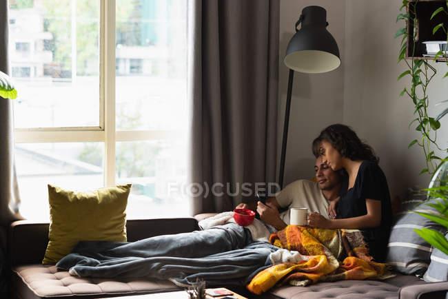 Couple utilisant un téléphone portable tout en prenant un café dans le salon à la maison — Photo de stock
