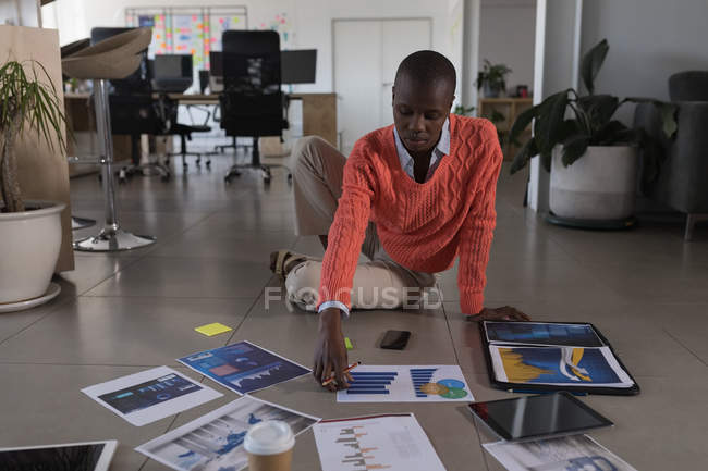 Female executive working on floor in office — Stock Photo