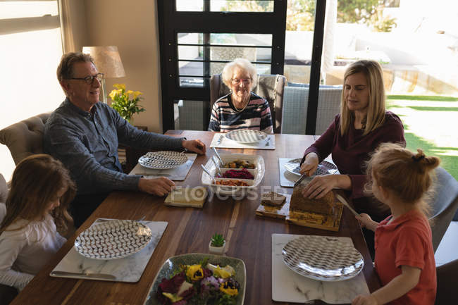 Multi generation family having food on dining table at home — Stock Photo