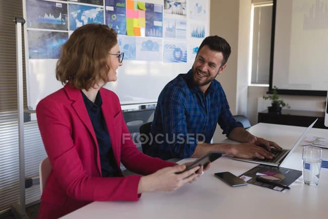Улыбающиеся бизнесмены разговаривают друг с другом в офисе — стоковое фото