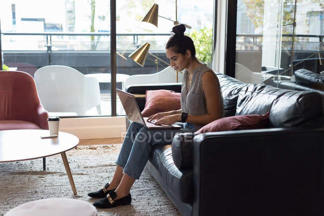 Vista laterale della donna d'affari che utilizza il computer portatile in ufficio — Foto stock