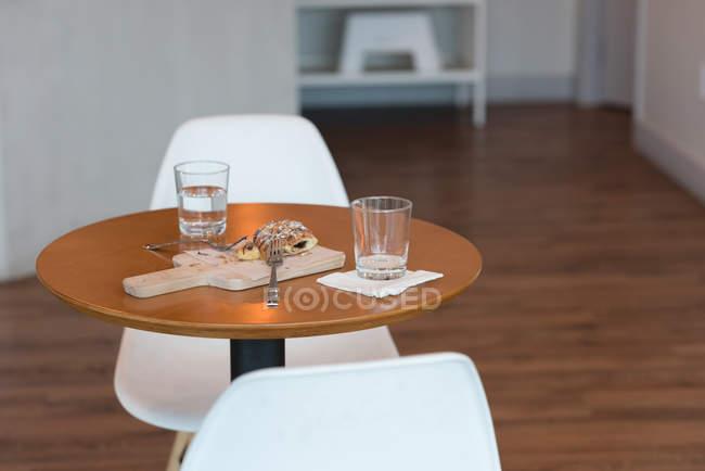 Glas Wasser und süße Speisen auf dem Tisch im Café — Stockfoto