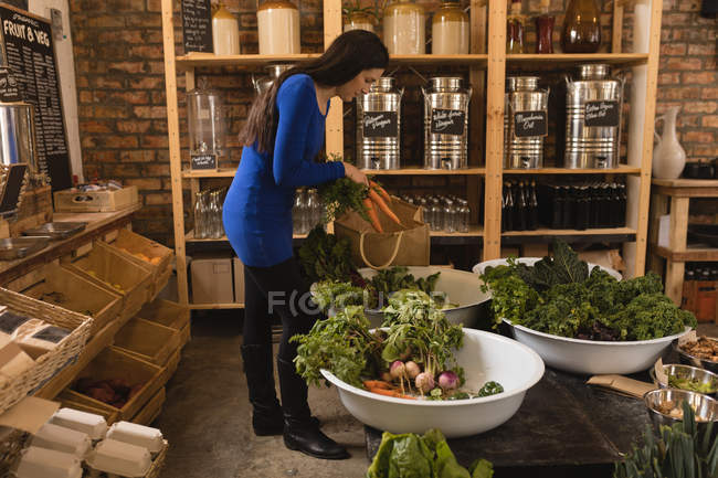 Woman putting vegetable in shopping bag at supermarket — Stock Photo