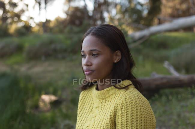 Задумчивая женщина, смотрящая в лес — стоковое фото