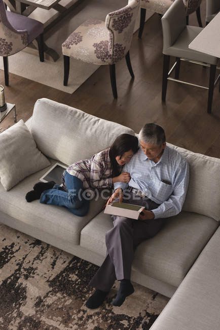 Grandfather and granddaughter using digital tablet on sofa in living room at home — Stock Photo
