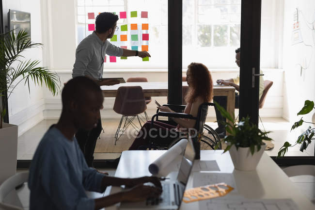 Executives discussing on sticky notes in office — Stock Photo