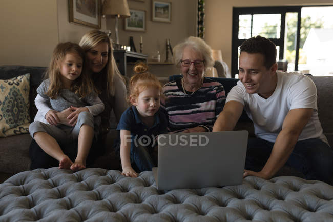 Multi generation family using laptop on sofa in living room at home — Stock Photo
