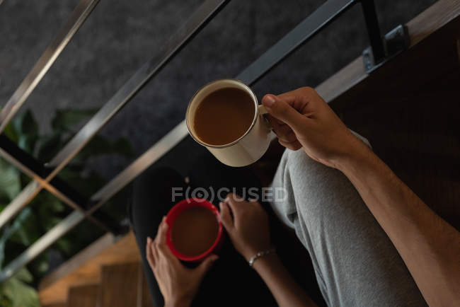 Mid section of couple holding coffee in stairs at home — Stock Photo