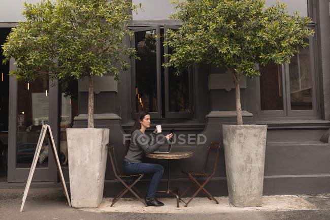 Красивая женщина с помощью мобильного телефона имея кофе в кафе на открытом воздухе — стоковое фото