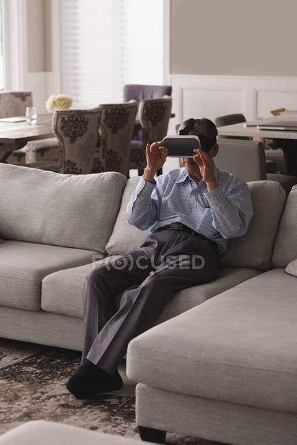 Senior man using virtual reality headset on sofa in living room at home — Stock Photo