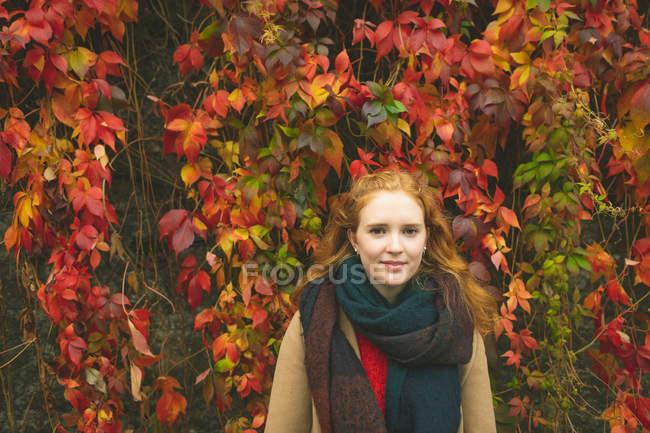 Pelirroja de pie contra planta enredadera durante el otoño - foto de stock