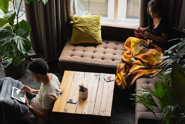 Couple using mobile phone and digital tablet while having coffee in living room at home — Stock Photo