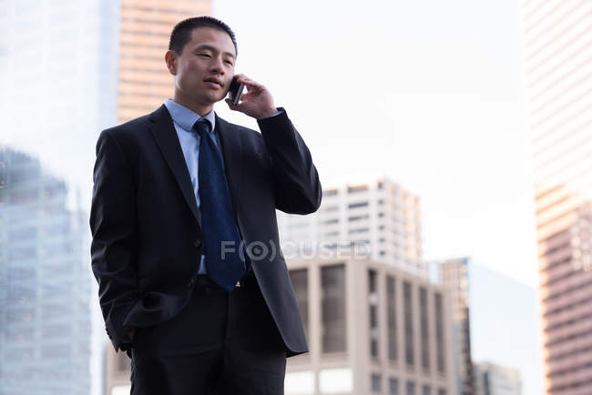 Businessman talking on mobile phone in balcony at hotel — Stock Photo
