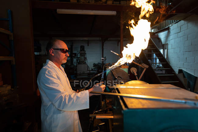 Side view of male worker using welding torch in glass factory — Stock Photo