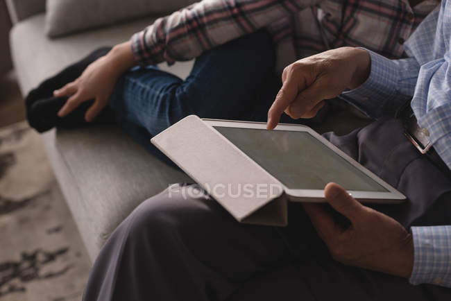 Close-up of grandfather and granddaughter using digital tablet on sofa in living room at home — Stock Photo