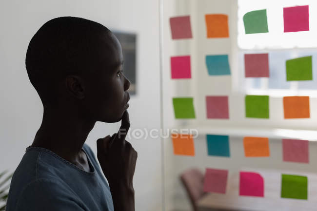 Thoughtful executive looking at sticky notes in office — Stock Photo